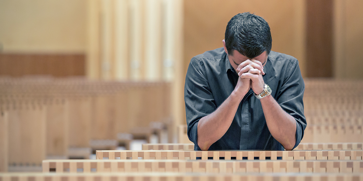 web3 young man praying church blue shirt shutterstock